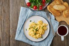Взбитые яйца, омлет, взгляд сверху, космос экземпляра Завтрак со все-зажаренными яйцами, чашка чаю, томаты на старом деревянном с стоковые фото
