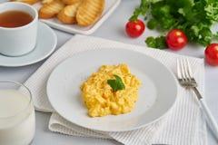 Взбитые яйца, омлет, взгляд со стороны Завтрак со все-зажаренными яйцами, стекло молока, томатов на белой предпосылке стоковые изображения rf