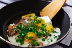 Взбитые яйца с беконом и луками в процессе подготовки Стоковое Изображение RF
