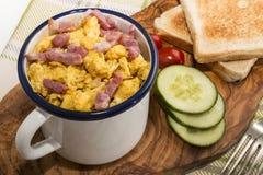 Взбитые яйца с зажаренным в духовке беконом в кружке эмали стоковая фотография