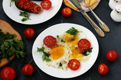 Взбитые яйца с томатами вишни расположены на белой плите на темной предпосылке, фото там испекли баклажаны, петрушку стоковые изображения rf