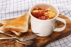 Взбитые яйца с томатами и зажаренным беконом в чашке стоковое изображение