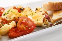 Взбитые яйца с томатами и зажаренным беконом, земным перцем и стоковые фото