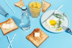 Взбитые яйца, умасленные тосты и напитки на голубой таблице Взгляд сверху завтрака стоковое изображение