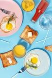 Взбитые яйца, умасленные тосты и напитки на голубой таблице Взгляд сверху завтрака стоковое изображение rf