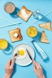Взбитые яйца, умасленные тосты и напитки на голубой таблице Взгляд сверху завтрака стоковые фото
