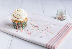 Взбрызнутое ванильное пирожное на белом деревянном столе стоковые фотографии rf