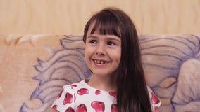 Взволнованности ребенка Маленькая девочка в красивом платье на кресле Девушка в платье с сердцами сток-видео