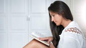 Взгляда со стороны кавказская привлекательная задумчивая женщины книга чтения восторженно дома видеоматериал