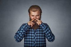 Взгляды носа щипков человека с отвращением что-то воняют плохим запахом стоковая фотография