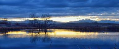 Взгляды пути пруда Josh's идя, отражая захода солнца в Broomfield Колорадо окруженном Cattails, равнин и Ла скалистой горы стоковое изображение