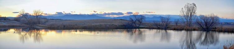 Взгляды пути пруда Josh's идя, отражая захода солнца в Broomfield Колорадо окруженном Cattails, равнин и Ла скалистой горы стоковое фото rf