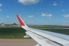 Взгляд авиапорта и воздушных судн, голубого неба и облаков от иллюминатора авиалайнера пассажира Стоковая Фотография