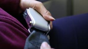 Взгляд азиатской женщины прикрепляя ее ремень безопасности, внутри самолета сток-видео