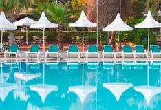 Взгляд бассейна гостиницы со стульями и зонтиками стоковое фото
