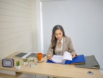 Взгляд бизнес-леди к отчет о ее стол стоковое фото