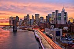 Взгляд более низкого Манхаттана с Бруклинским мостом на заходе солнца, Нью-Йорком Стоковое Изображение