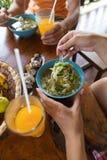Взгляд верхнего угла женщины есть палочку лапшей и выпивая апельсиновый сок сидя на девушке таблицы непознаваемой Стоковые Изображения RF