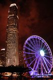 Взгляд вечера от обваловки к колесу Ferris с многоэтажным зданием Hong Kong Стоковые Фото