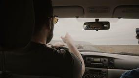 Взгляд внутри автомобиля Человек 2 управляя автомобилем через пустую дорогу Друзья в солнечных очках путешествуя совместно сток-видео
