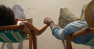 Взгляд высокого угла Афро-американских пар ослабляя с рука об руку внутри шезлонгом на пляже видеоматериал