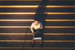 Взгляд высокого угла бизнесмена сидя на лестницах, работая на ноутбуке и показывая большие пальцы руки вверх на заходе солнца стоковая фотография rf
