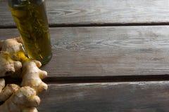 Взгляд высокого угла бутылки масла имбирями на таблице Стоковые Фото