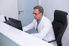 Взгляд высокого угла дантиста сидя компьютером Стоковая Фотография RF