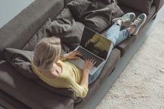 Взгляд высокого угла девушки используя компьтер-книжку Стоковые Фотографии RF