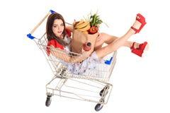 Взгляд высокого угла девушки усмехаясь на камере пока держащ продуктовые сумки и сидящ в изолированной вагонетке покупок на белиз Стоковое Фото