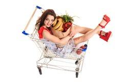 Взгляд высокого угла девушки усмехаясь на камере пока держащ продуктовые сумки и сидящ в изолированной вагонетке покупок на белиз Стоковое Изображение