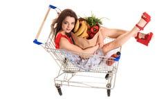 Взгляд высокого угла девушки усмехаясь на камере пока держащ продуктовые сумки и сидящ в изолированной вагонетке покупок на белиз Стоковое Изображение RF