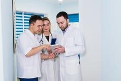 Взгляд высокого угла 3 докторов в белых пальто имея переговор на зале больницы стоковое фото rf