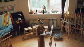 Взгляд высокого угла женского художника работая в workroom самостоятельно крася с щеткой и цветами на палитре Деревянные мольберт акции видеоматериалы