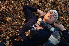 Взгляд высокого угла женщины с руками за головой лежа на сухих листьях Стоковое Изображение RF
