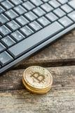 Взгляд высокого угла золотого Bitcoin чеканит около черной клавиатуры ПК Стоковые Изображения RF