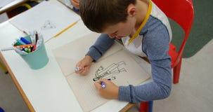 Взгляд высокого угла кавказского чертежа школьника на тетради в классе 4k видеоматериал