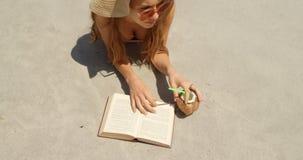 Взгляд высокого угла кавказской женщины в шляпе читая книгу на пляже 4k акции видеоматериалы