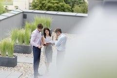 Взгляд высокого угла коллег обсуждая над документами на террасе офиса стоковое фото