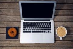 Взгляд высокого угла компьтер-книжки с донутом кофейной чашки Стоковая Фотография
