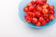 Взгляд высокого угла к зрелым ягодам вишни с капельками воды в голубую плиту на белой предпосылке Стоковое Изображение