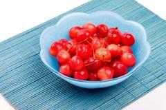 Взгляд высокого угла к зрелым ягодам вишни с капельками воды в голубую плиту на бамбуковой циновке Стоковые Изображения RF