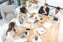 взгляд высокого угла многокультурной группы в составе бизнесмены обсуждая работу Стоковое фото RF