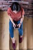 Взгляд высокого угла молодой женщины используя планшет пустого экрана цифровой пока сидящ на лестницах в офисном здании стоковые фото