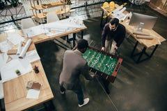 взгляд высокого угла молодых архитекторов играя футбол таблицы в офисе вполне  Стоковая Фотография RF