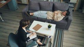 Взгляд высокого угла подростка говоря с психологом лежа на кресле в офисе видеоматериал