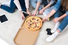 взгляд высокого угла подруг есть пиццу дома Стоковое Изображение