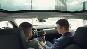 Взгляд высокого угла работника автосалона говоря к клиенту сидя внутри автомобиля предпринимательского класса, касающего пульта у видеоматериал