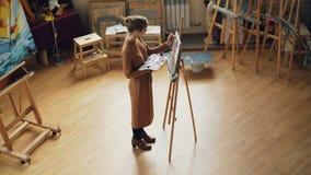 Взгляд высокого угла художника молодой женщины работая в положении студии перед мольбертом и крася удержание щетки и сток-видео