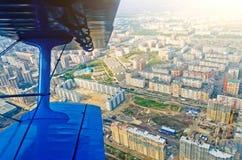 Взгляд в самолете иллюминатора самолет-биплана воздушных судн турбовинтового самолета на улицах и домах города Стоковое Изображение RF